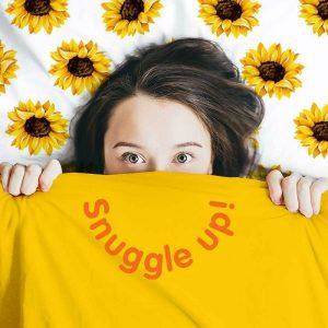 Snuggle Up lady hiding under doona