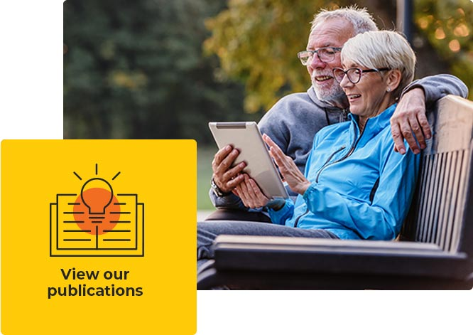 A couple sitting on a park bench looking at an iPad - View our Publications