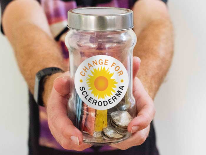 A jar with money and a sticker with Change for Scleroderma