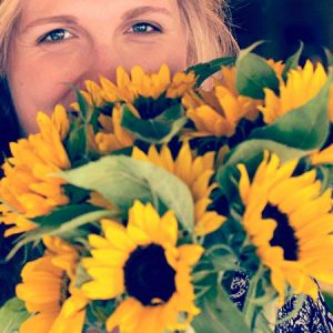 A lady holding a bunch of sunflowers near her face