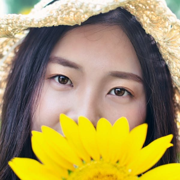 Young Asian woman wearing a straw hat outdoors, hiding part of her face behind a sunflower